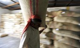 Un trabajador transporta un saco de café en una bódega de la Federación Nacional de Cafeteros de Colombia en Puerto Bello, ene 29 2014. Colombia debería liberar sus exportaciones de café para convertirse en abastecedor de diferentes calidades y abrir nuevos mercados, una decisión que contribuiría a mejorar los ingresos de los productores y del país, dijo el lunes el líder de los exportadores privados de café. REUTERS/Jose Miguel Gomez