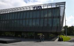 Members of the media walk in front of the headquarters of soccer's international governing body FIFA in Zurich, Switzerland, May 27, 2015. REUTERS/Ruben Sprich
