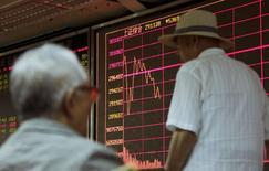 El banco central chino anunció el miércoles que había realizado  una inyección de 140.000 millones de yuanes (21.800 millones de dólares) en operaciones de liquidez a corto plazo (SLOs, por sus siglas en inglés) en el mercado interbancario. En la imagen, un inversor pasa junto a un panel electrónico en la bolsa de Shanghái, el  26 de agosto de 2015. REUTERS/Jason Lee
