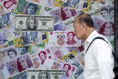 Un hombre camina junto a un aviso que promociona servicios cambiarios para el dólar estadounidense, el yuan y el euro, en una casa de cambio en Hong Kong, China, 13 de agosto de 2015. El dólar recortó sus ganancias frente al yen el miércoles debido a que los mercados de acciones chinas y europeas perdían terreno pese a las medidas de alivio de China, y a la mayoría de los inversores les preocupaba el panorama para la economía global. REUTERS/Tyrone Siu