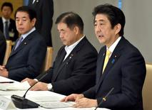 Japan's Prime Minister Shinzo Abe (R) speaks during a meeting of Cabinet ministers on a new National Stadium construction plan for the 2020 Tokyo Olympics at Abe's official residence in Tokyo on August 28, 2015 while Olympics Minister Toshiaki Endo (C) and Education Minister Hakubun Shimomura (L) attend. REUTERS/Kazuhiro Nogi/Pool