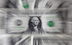 Долларовые банкноты. Варшава, 8 августа 2011 года. Курс доллара к корзине шести основных валют держится вблизи отмеченного в четверг недельного максимума за счет экономической статистики США и снижения спроса на иену как низкорискованный актив. REUTERS/Kacper Pempel