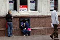 Una mujer usando un cajero automático en una sucursal del banco HSBC en Loughborough, Inglaterra, mayo 11 2011. Miles de británicos se quedaron este viernes sin recibir sus salarios debido a una falla en el mayor banco de Europa, el HSBC, que impidió que algunos de sus clientes empresariales pudieran realizar los desembolsos.  REUTERS/Darren Staples