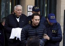Argentine businessmen Mariano Jinkis (C) and his father Hugo (L, back) who are wanted by U.S. prosecutors in a FIFA bribery investigation, are escorted by police officers after they turned themselves in on to authorities in Buenos Aires, Argentina, June 18, 2015. REUTERS/Enrique Marcarian