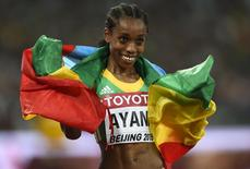 Almaz Ayana of Ethiopia poses with her national flag after winning the women's 5000 metres final at the 15th IAAF Championships at the National Stadium in Beijing, China August 30, 2015.  REUTERS/Dylan Martinez