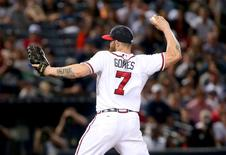 Atlanta Braves left fielder Jonny Gomes (7) pitches in the ninth inning of their game against the New York Yankees at Turner Field. The Yankees won 15-4. Jason Getz-USA TODAY Sports