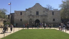 Visitors walk at the entrance to the Alamo, the most-visited tourist site in the state, in San Antonio, Texas March 2, 2015. REUTERS/Lisa Maria Garza