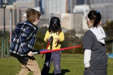 "A child wearing a Darth Vader mask participates in a light saber duel with other children after the live internet unveiling of new light saber toys from the film ""Star Wars - The Force Awakens"" in Sydney, September 3, 2015. REUTERS/Jason Reed"