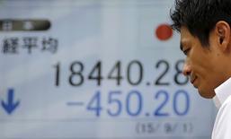 Un hombre camina junto a un tablero electrónico que muestra el índice Nikkei de Japón, afuera de una correduría en Tokio, 1 de septiembre de 2015. El índice Nikkei de la bolsa de Tokio subió el jueves luego de que los inversores compraron acciones golpeadas por el temor a una desaceleración global liderada por China. REUTERS/Toru Hanai