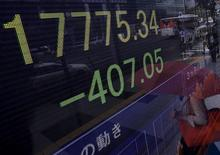 Un peatón es reflejado en un tablero electrónico que muestra el índice Nikkei afuera de una correduría en Tokio, Japón, 4 de septiembre de 2015. El índice Nikkei de la bolsa de Tokio cayó el viernes a un mínimo en siete meses en medio de la cautela de los inversores antes de la publicación de unos datos de empleo en Estados Unidos más tarde en el día. REUTERS/Yuya Shino
