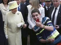 A local youth takes a selfie in front of Britain's Queen Elizabeth in St George's indoor market in Belfast, Northern Ireland June 24, 2014. REUTERS/Peter Macdiarmid/Pool