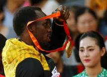 Usain Bolt of Jamaica removes his gold medal which is not engraved with his name as he poses on the podium after the men's 4 x 100 metres relay event during the 15th IAAF World Championships at the National Stadium in Beijing, China, August 30, 2015.    REUTERS/Kai Pfaffenbach