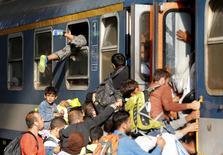 """Мигранты штурмуют поезд на вокзале """"Келети"""" в Будапеште 3 сентября 2015 года.  Президент Еврокомиссии Жан-Клод Юнкер представит план борьбы с миграционным кризисом в Евросоюзе во время ежегодного обращения к Европарламенту в среду.    REUTERS/Laszlo Balogh"""