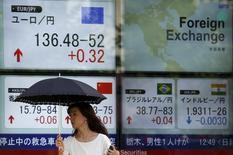 """Una mujer camina junto a un tablero electrónico que muestra la tasa cambiaria entre varias monedas, entre ellas el yen contra el euro, afuera de una correduría en Tokio, 13 de julio  de 2015. El yen caía el miércoles por un alza de los mercados globales que redujo la demanda por activos de refugio, mientras que el euro también se debilitaba luego de que los inversores hicieran una pausa en la disolución de las riesgosas operaciones de """"carry trade"""" financiadas con la moneda europea. REUTERS/Issei Kato"""