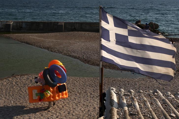 A beach vendor walks on the beach while a Greek flag flutters at a southern Athens suburb July 30, 2015. Temperatures in Greece have approached 40 degrees Celsius in recent days as a summer heatwave grips the country. REUTERS/Yiannis Kourtoglou