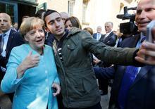 Un migrante se toma una selfie con la canciller alemana Angela Merkel a las afueras de un campo de refugiados cerca de la Oficina Federal de Migración y Refugiados en el distrito de Spandau, en Berlín, el 10 de septiembre de 2015. La canciller alemana, Angela Merkel, instó a Facebook a hacer más contra comentarios racistas y publicaciones de odio, en comentarios publicados el viernes en un periódico regional. REUTERS/Fabrizio Bensch