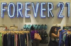 Una mujer compra ropa en la tienda Forever 21, en Nueva York, 19 de agosto de 2013. La confianza del consumidor estadounidense cayó en los primeros días de este mes a su menor nivel desde septiembre del año pasado, mostró un sondeo publicado el viernes. REUTERS/Lucas Jackson