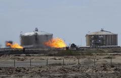 Избыточный газ сжигается на трубопроводе на месторождении Зубайр к юго-востоку от Багдада 5 марта 2015 года. Ирак предупредил иностранные нефтяные компании, разрабатывающие месторождения на юге страны, что им нужно будет снизить инвестиции в следующем году, потому что бюджет на оплату их услуг сократился из-за падения цен на нефть. REUTERS/Essam Al-Sudani
