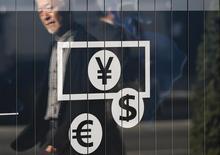 Un peatón se refleja en un letrero que muestra los símbolos del yen, el dólar y el euro, afuera de un banco en Tokio, 27 de noviembre de 2014. Las bolsas de Asia cedían el martes en medio de la cautela antes de la reunión que la Reserva Federal de Estados Unidos sostendrá esta semana, y el yen subía después de que el Banco de Japón mantuvo su política monetaria estable. REUTERS/Issei Kato