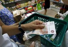 Женщина расплачивается пятитысячной купюрой в продуктовом магазине в Красноярске. 6 августа 2015 года. Индекс потребительских цен в РФ с 8 по 14 сентября 2015 года составил 0,1 процента по сравнению с 0,2 процента в предыдущие две недели, сообщил Росстат. REUTERS/Ilya Naymushin