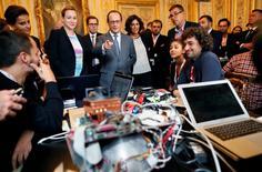 """François Hollande à l'Elysée avec de jeunes employés du secteur du numérique à l'occasion du lancement d'un réseau de formations labélisées """"Grande école du numérique"""" pour améliorer les compétences dans un secteur très créateur d'emplois. /Photo prise le 17 septembre 2015/REUTERS/Ian Langsdon/Pool"""