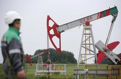 A worker looks at a pump jack at an oil field Buzovyazovskoye owned by Bashneft company north from Ufa, Bashkortostan, Russia, July 11, 2015. Russian President Vladimir Putin has signed a decree on transferring a 25 percent plus one share stake in medium-sized oil producer Bashneft to the region of Bashkortostan, Interfax news agency said on June 22, 2015. Picture taken July 11, 2015.  REUTERS/Sergei Karpukhin