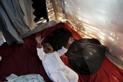 Lisania Disten yawns while resting on a bed inside a makeshift tent at a refugee camp for Haitians returning from the Dominican Republic and where she lives with her family on the outskirts of Anse-a-Pitres, Haiti, September 7, 2015. REUTERS/Andres Martinez Casares