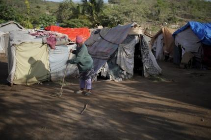 A woman sweeps the ground outside makeshift tents at a refugee camp for Haitians returning from the Dominican Republic on the outskirts of Anse-a-Pitres, Haiti, September 7, 2015. REUTERS/Andres Martinez Casares