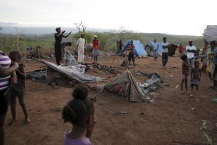 Residents stand around an uninhabited makeshift tent that was torn down at a refugee camp for Haitians returning from the Dominican Republic on the outskirts of Anse-a-Pitres, Haiti, September 7, 2015. REUTERS/Andres Martinez Casares