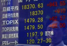Un peatón se refleja en una pantalla que muestra el índice Nikkei y la tasa cambiaria entre el dólar estadounidense y el yen, afuera de una correduría en Tokio, Japón, 9 de septiembre de 2015. El índice Nikkei de la bolsa de Tokio rebotó desde un mínimo en dos semanas que anotó el viernes temprano luego de que los inversores compraron acciones de empresas inmobiliarias y financieras por la esperanza de que el Banco de Japón podría relajar su política monetaria tan pronto como el próximo mes. REUTERS/Yuya Shino