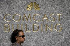 Una mujer pasa por delante del logo de NBC y Comcast en la plaza Rockefeller en Nueva York el 23 de julio de 2015. El grupo Comcast Corp anunció el lunes que adquirirá una participación mayoritaria en Universal Studios Japan por 1.500 millones de dólares, su mayor inversión fuera de Estados Unidos y parte de una agresiva expansión a nivel global de su negocio de parques temáticos. REUTERS/Brendan McDermid