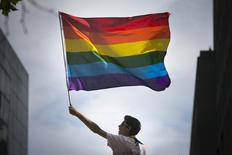 A man waves a rainbow flag while observing a gay pride parade in San Francisco, California June 28, 2015. REUTERS/Elijah Nouvelage