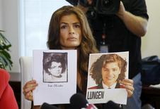 Former Mrs America Lisa Christie, who alleges misconduct by Bill Cosby, holds up photos of her younger self during a news conference at the law office of attorney Gloria Allred in Los Angeles, September 30, 2015. REUTERS/Danny Moloshok