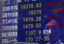 Un peatón se refleja en una pantalla que muestra el índice Nikkei y la tasa cambiaria entre el dólar estadounidense y el yen, afuera de una correduría en Tokio, Japón, 9 de septiembre de 2015. Las bolsas de Asia subían el jueves, impulsadas por las ganancias de la sesión anterior en los mercados de renta variable después de su trimestre más débil en cuatro años, mientras que unas encuestas que confirmaron una debilidad persistente en el sector manufacturero chino fueron tomadas con calma. REUTERS/Yuya Shino