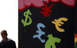 Символы валют у пункта обмена валюты в Дублине 22 октября 2014 года. Курс доллара растет накануне публикации отчета о занятости в США, который повлияет на решение ФРС о повышении процентных ставок. REUTERS/Cathal McNaughton
