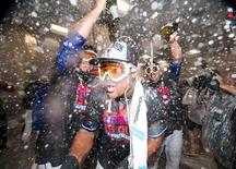Oct 4, 2015; Arlington, TX, USA; Texas Rangers starting pitcher Yovani Gallardo (L), third baseman Adrian Beltre (C), and starting pitcher Derek Holland (R) celebrate after defeating the Los Angeles Angels 9-2 to clinch the American League West division at Globe Life Park in Arlington. Mandatory Credit: Jerome Miron-USA TODAY Sports