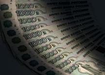 1000-рублевые купюры. Москва, 17 февраля 2014 года. Рубль подорожал на торгах четверга вслед за нефтью, сократив  как и она диапазон внутридневных колебаний; активность также была ограничена ожиданиями публикации протоколов последнего заседания ФРС, которая может прояснить ситуацию со сроками начала повышения процентной ставки по доллару. REUTERS/Maxim Shemetov