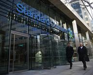People walk past the head office of Standard Chartered bank in the City of London February 27, 2015