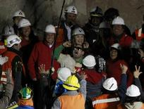 Miner Mario Sepulveda (C) celebrates as President Sebastian Pinera, rescue workers and government officials watch, when he became the second miner to be hoisted to the surface in Copiapo October 13, 2010. REUTERS/Ivan Alvarado