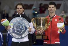 Winner Novak Djokovic (R) of Serbia and runner-up Rafa Nadal of Spain pose with their trophies during the award ceremony after the men's singles final match at the China Open Tennis Tournament in Beijing, China, October 11, 2015. REUTERS/Stringer