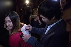 "Filipino boxing superstar Manny Pacquiao signs an autograph while he attends the exhibition of Philippine Gold ""Treasures of Forgotten Kingdoms"" in New York, October 12, 2015. REUTERS/Eduardo Munoz"