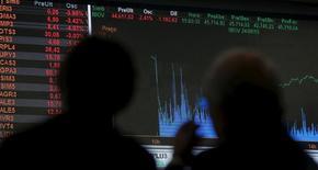 Unas personas observan un panel con información bursátil en la Bolsa de Valores de Sao Paulo, ago 24, 2015. El principal índice de acciones de Brasil operaba a la baja el martes, tras una racha ganadora que duró nueve sesiones, por la presión de las bajas de los ADR brasileños de la víspera y la fuerte baja de los papeles de los bancos por perspectivas poco favorables para el sector. REUTERS/Paulo Whitaker