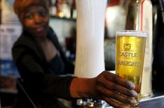 Una camarera sirve una cerveza producida por SABMiller en Ciudad del Cabo. Las dos mayores cerveceras del mundo acordaron el martes crear una compañía que fabricará casi un tercio de la cerveza del mundo, después de que SABMiller aceptó una oferta por más de 100.000 millones de dólares de su rival Anheuser-Busch InBev. REUTERS/Mike Hutchings
