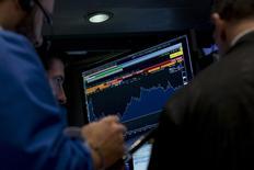Трейдеры на фондовой бирже в Нью-Йорке. 7 октября 2015 года. Фондовые рынки США снизились во вторник за счет данных, подтвердивших замедление роста китайской экономики, и нового падения котировок биотехнологических компаний. REUTERS/Brendan McDermid