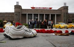 """Пара кроссовок, принадлежавщих уличному торговцу, на месте взрыва в Анкаре. 12 октября 2015 года. Премьер-министр Турции Ахмет Давутоглу сказал в интервью Рейтер в среду, что некоторые из подозреваемых в причастности ко взрывам в Анкаре, унесшим жизни 97 человек, провели много месяцев в Сирии и могут быть связаны с """"Исламским государством"""" или курдскими повстанцами. REUTERS/Umit Bektas"""