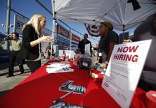 Personas revisan los puestos en una feria de trabajos para veteranos militares, en Carson, California, 3 de octubre de 2014. La cantidad de estadounidenses que solicitaron por primera vez el subsidio por desempleo cayó nuevamente a un mínimo de 42 años la semana pasada, lo que sugiere que el mercado laboral sigue fuerte a pesar de una desaceleración abrupta en el crecimiento del empleo en los últimos dos meses. REUTERS/Lucy Nicholson