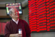 Un inversor mira las pantallas electrónicas bursátiles situadas en Nanjing, provincia de Jiangsu, en China, el 12 de octubre de 2015. Los principales índices bursátiles de China treparon más de un 1 por ciento el martes, luego de que un repunte de los valores de baja capitalización reavivó el interés de los inversores, impulsando a todos los sectores en la última hora de negociación. REUTERS/China Daily