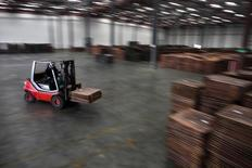 Un trabajador carga cátodos de cobre en un almacén cerca del puerto Yangshan Deep Water, al sur de Shanghái, 23 de marzo de 2012.  La producción de cobre refinado en China subió un 2,3 por ciento en septiembre frente al mes previo, alcanzando un pico de tres meses por el aumento de la actividad en algunas fundiciones nuevas y mayores suministros del metal sin refinar. REUTERS/Carlos Barria