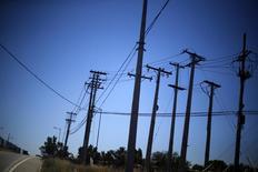 """Unos cables de alta tensión en una autopista en Santiago, nov 7, 2014. Las tardías lluvias que dejará el fenómeno de """"El Niño"""" en Chile este año llevarán a un importante aumento de los niveles en los embalses y a un retraso en la temporada de deshielos, efectos que ayudarían a reducir los costos de generación de las empresas eléctricas, dijeron analistas.     REUTERS/Ivan Alvarado"""