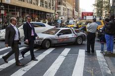 """Pedestrians stop to look at and photograph a DeLorean Motor Company DMC-12 customized to look identical to the car used in the film """"Back to the Future Part II"""" and that will be part of a Lyft promotion in New York, October 21, 2015. Today marks the day that the movie's main character, Marty McFly, travelled to the future in the 1989 """"Back to the Future"""" sequel. REUTERS/Lucas Jackson"""